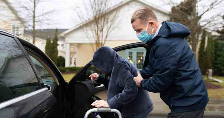 A man in a rain jacket and a mask helps his mother into the passenger seat of a car