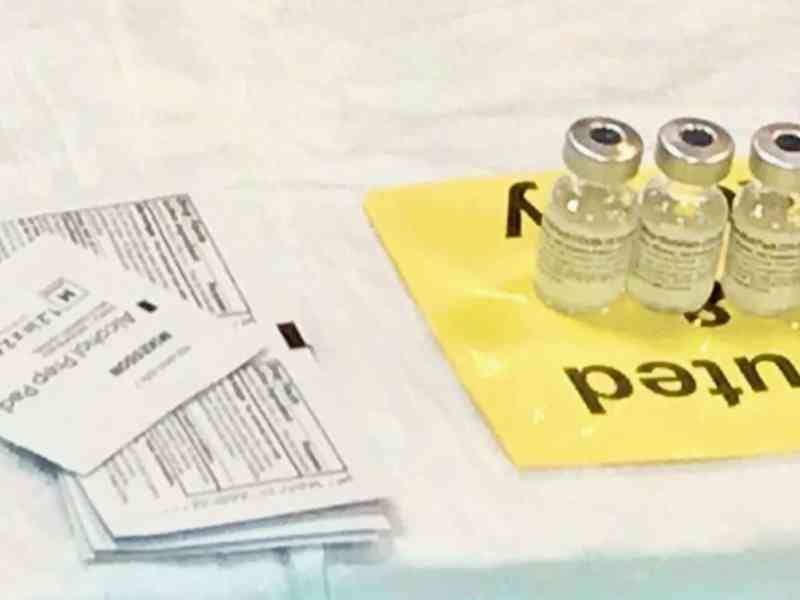 Vaccine vials and paper on a table