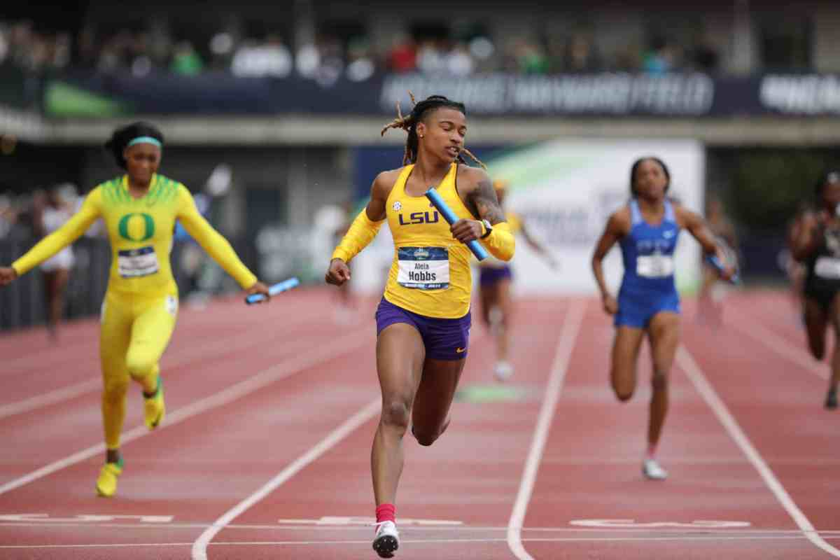 photo shows a college women's track meet with three racers pulling ahead of the others