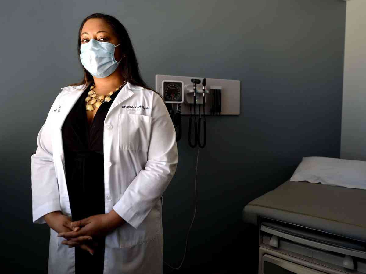 shows an Black woman in a black dress, white coat and facemask standing in a medical exam room.