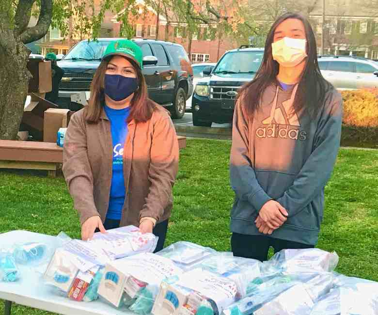 Two women wearing face masks stand behind a table to hand out bags of personal protective equipment