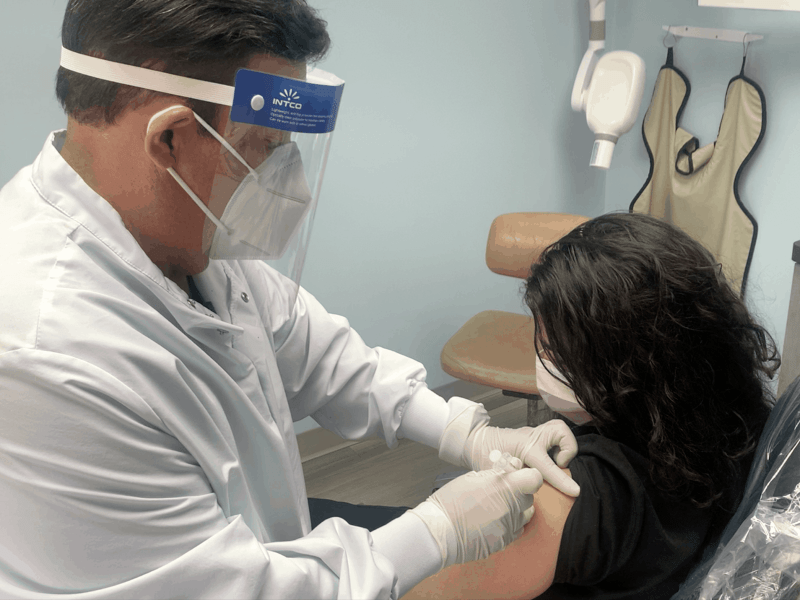 Dentist in face mask and shield gives a shot to a female patient