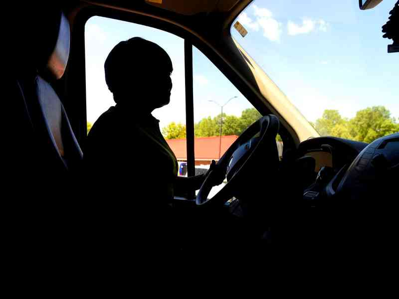 shows the silhouette of a woman who has long haul COVID who's driving a van