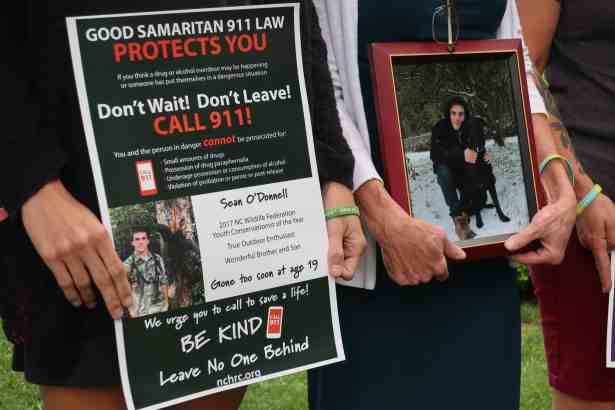 """shows hands of women holding up a framed photograph of a young man, another pair of hands holds up a poster of a young man. On the poster it reads: """"Gone too soon at age 19"""""""
