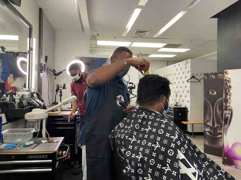 In a barbershop a man is standing and trimming another mans hair. The other man is sitting in a chair.