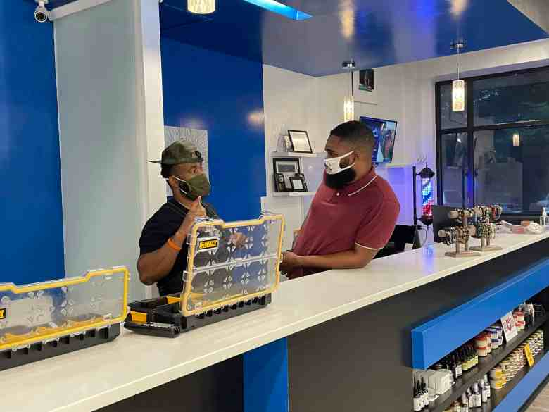 Two men with masks on conversing behind a counter.