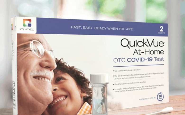 Shows a picture of a box with the test materials sitting on a wood counter in front of the box. The box reads: QuickVue At-Home OTC COVID-19 Test