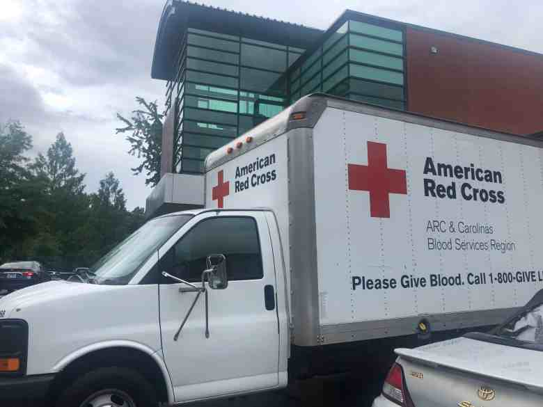 """An American Red Cross truck is stationed outside of a building. The truck reads """"American Red Cross ARC & Carolinas Blood Services Region. Please Give Blood. Call 1-800-GIVE LIFE"""