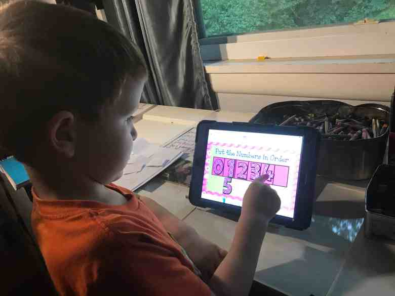 A kindergartener boy is learning about numbers on a iPad.