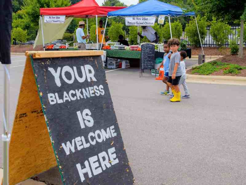 """Shows a black board that writes """"Your blackness is welcome here."""" Behind it are three young children walking by and two tents displaying vegetables"""