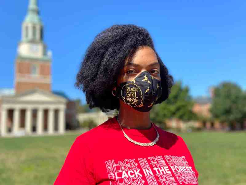 In this photo Houston Booth is wearing a mask on Wake Forest Campus in front of Wait Chapel, the Chapel is blurred in the background.