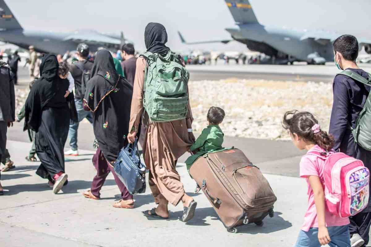 shows people in a line dragging suitcases and wearing backpacks as they walk toward large military transport planes in the distance