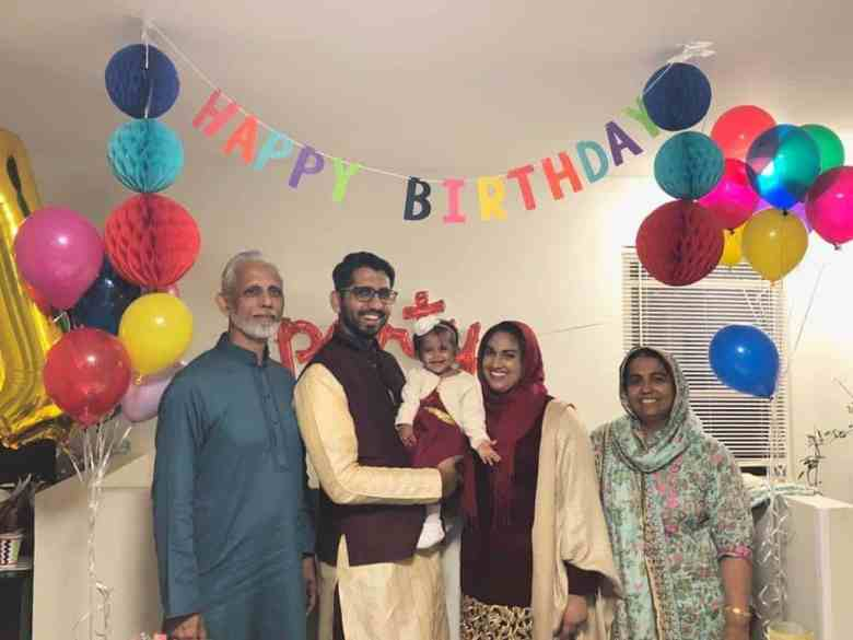 Some members of the Sidiqqui family at a birthday celebration, a happy birthday sign is hanging on top of them and balloons surrounding them.