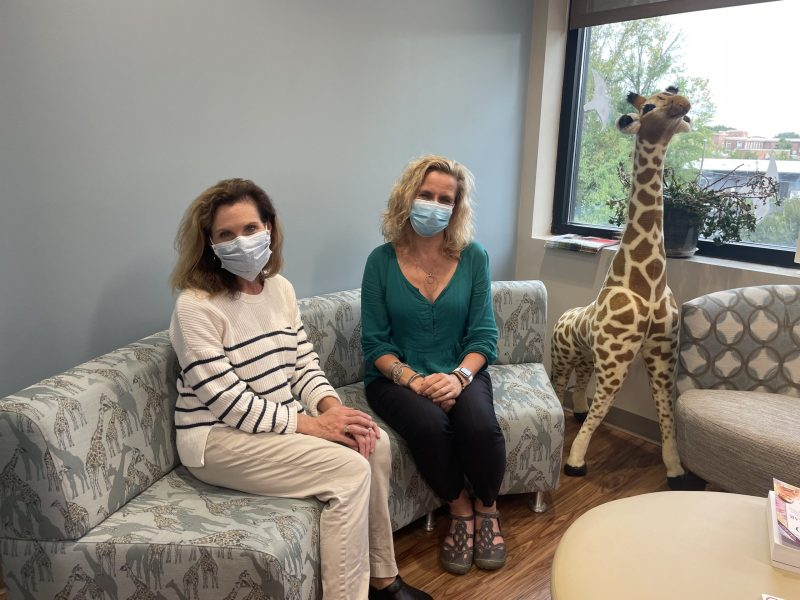 A woman with brown hair and a blue mask is seated on a couch with giraffes on it. Next to her is a blonde woman with a blue mask. There is a large giraffe stuffed animal on the floor next to them.