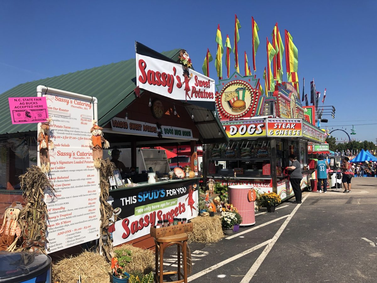 """We see two booths, one is Sassy's Sweet Potatoes, which advertises """"This spud's for you."""" There is another booth next to it that offers hot dogs and steak and cheese."""
