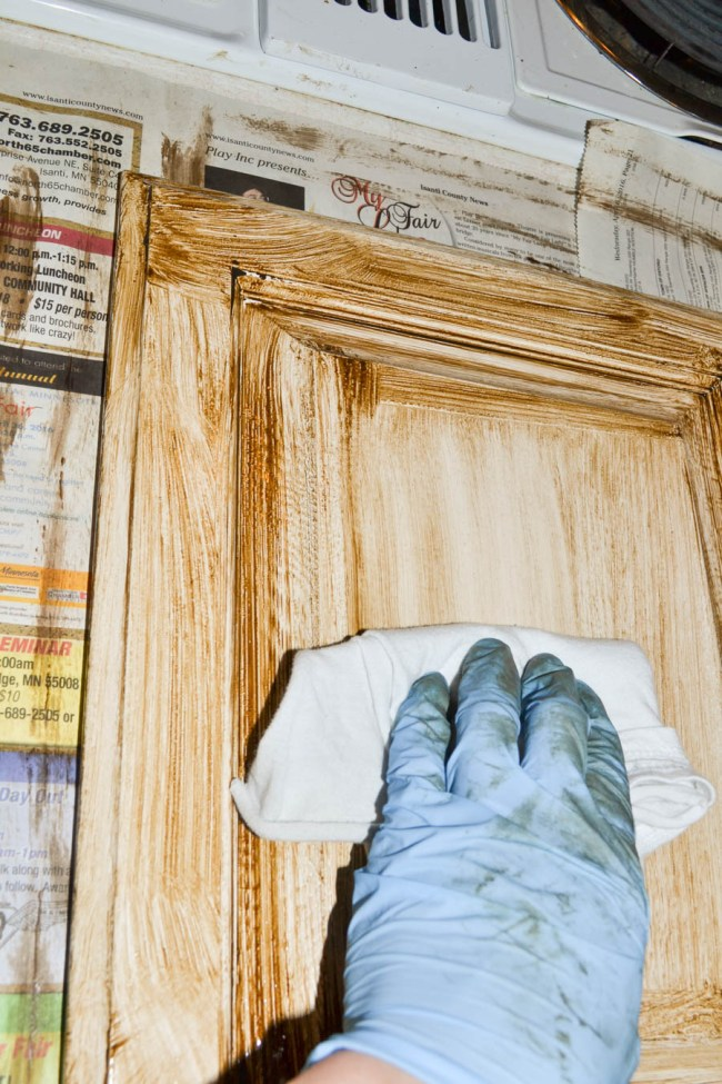 cabinet door covered in glaze being wiped off