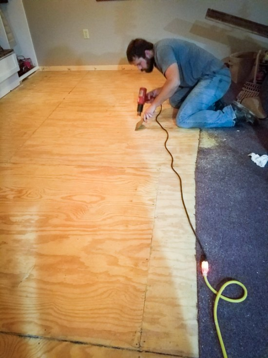 using a heat gun to prepare for laying interior brick tile