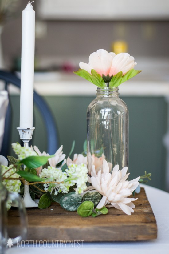 milk jar with pink flower and wood table runner