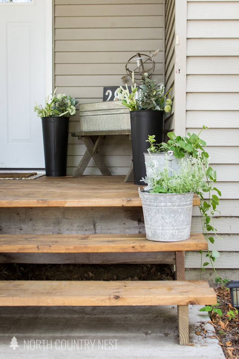 galvanized plants on porch stained honey teak