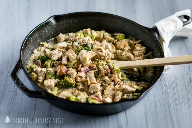 chicken dinner in iron skillet with wooden spoon