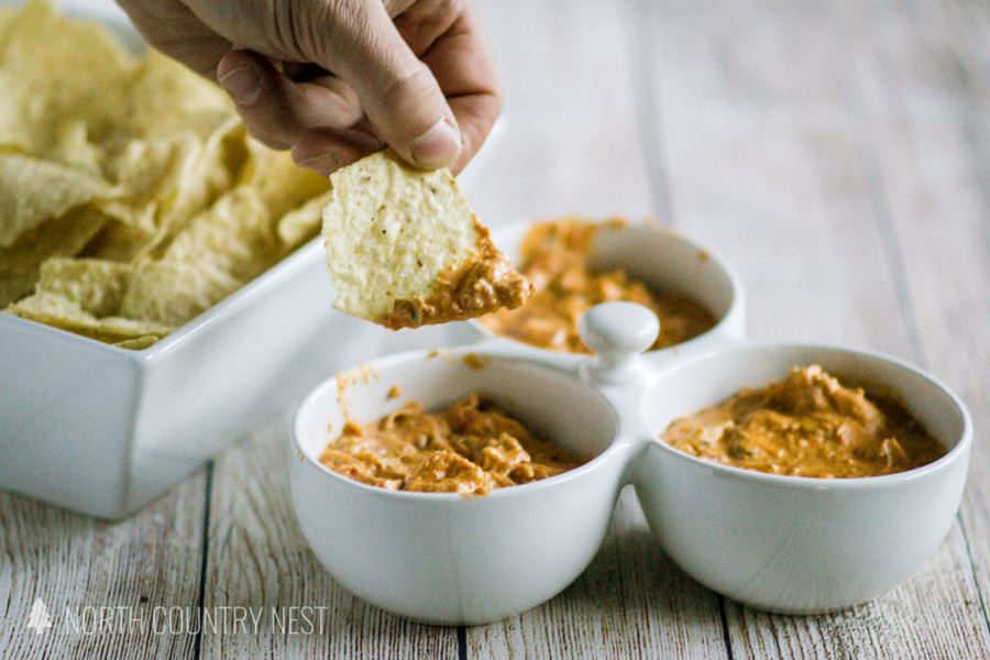 chip dipping into cheesy chicken taco dip