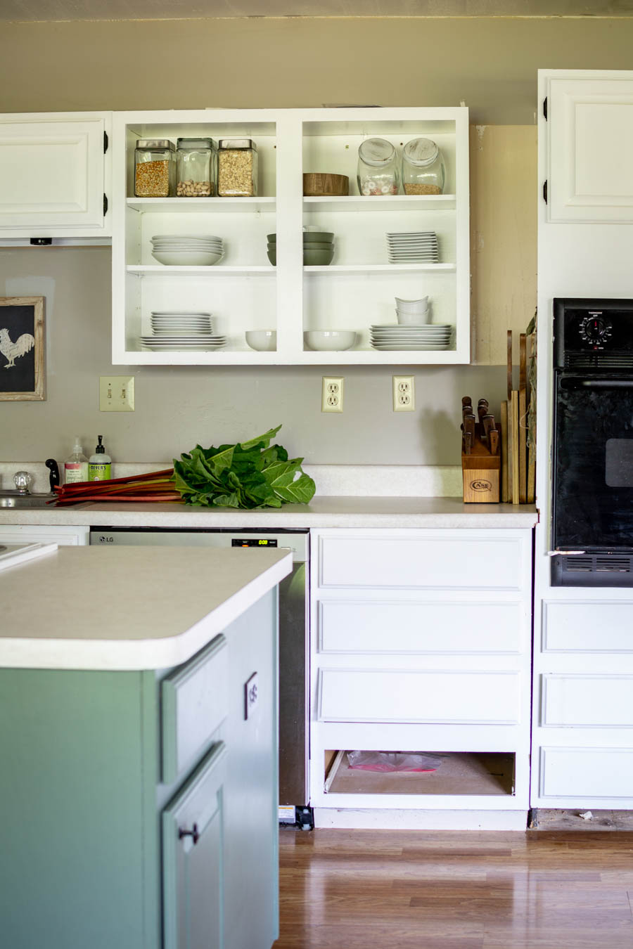 white kitchen cabinets with open shelving and green island