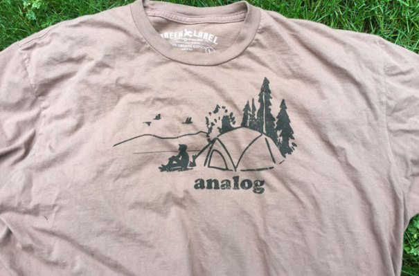 "Green Label offers a variety of hiking inspired t-shirts with slogans such as ""analog,"" ""It's just a hill, get over it,"" and ""Outsider."""