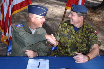 U.S. Air Force Gen. Gene Renuart, commander of USNORTHCOM, signs agreement Feb. 14, 2008, with Canadian Air Force Lt. Gen. Marc Dumais, commander of Canada Command (USNORTHCOM photo)