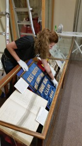 NHS Curator, Cathy Osterman installs a 1916 banner from the Rice County Fair when it was held in Northfield.