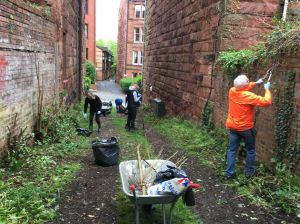 Volunteers in the lane, lopping greenery and generally clearing up.