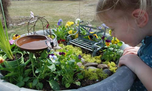 child looking into a fairy garden