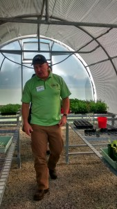Photo of Colin taking a tour of the greenhouse.
