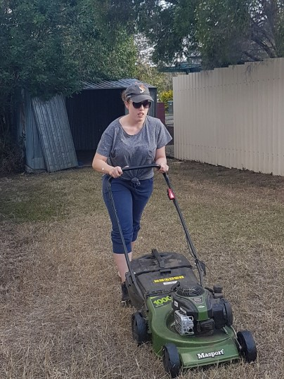 Student mowing a lawn in Monto