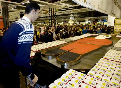 Sultan Kösen, the world's tallest man, unveils the world's largest gingerbread man at an Ikea store in Oslo, Thursday, Nov. 12 2009. The Swedish furniture chain's Oslo outlet says 8-foot-1-inch tall Sultan Koesen of Turkey presented the cookie that weighs 1,435 pounds (651 kilograms). It was baked in the traditional gingerbread man shape by a local bakery and beat the previous 2006 world cookie record of 1,307 pounds (593 kilograms) set in Smithville, Texas.