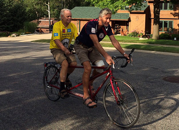 Photo: Leslee Lane Hoyum Harald Vik and guide/interpreter Ivar Wigaard demonstrate tandem bike riding technique for guests at a reception in Harald Vik's honor at the home of Marit and Orlyn Kringstad, Bloomington, Minn.