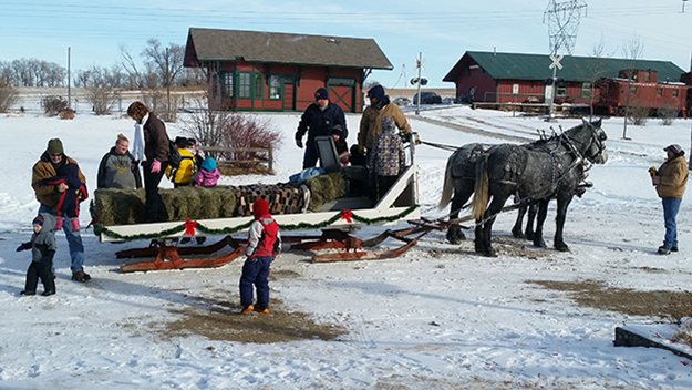 Photo: Ellen Schafer Sleigh rides for families were popular on the historic grounds of Buckstop Junction. Roy Bergquest is driving the team of horses with Larry Bergquest and son standing at right of photo.