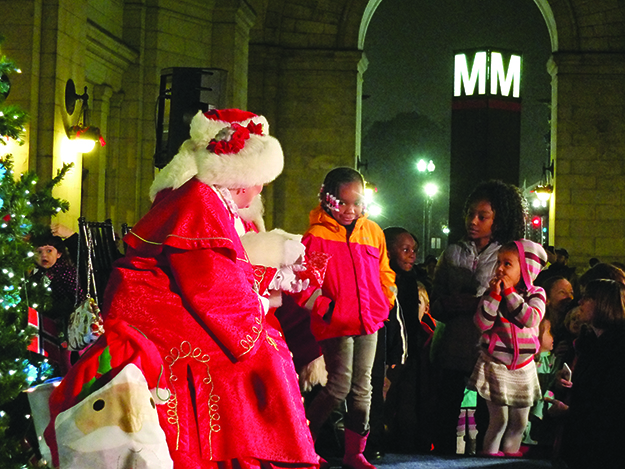 Photo: Bruce Guthrie Mrs. Claus hands out gifts to young Washingtonians.