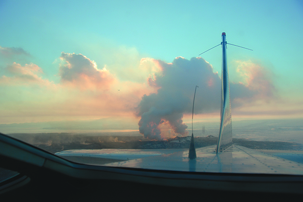 Photo: Emily C. Skaftun Iceland's newest volcano sends clouds of smoke to blot out the sun, as seen from the tail window of a Cessna.