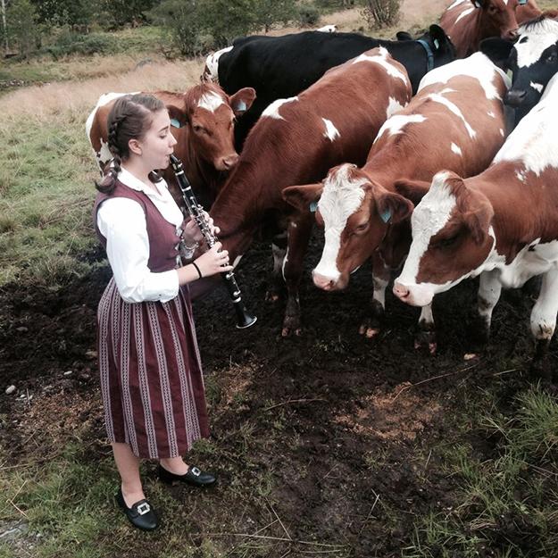 """Photos: Britt Eva Heggheim Dressed as a """"Budeie,"""" Jillian serenades the cows at Befring, her cousins' dairy farm."""