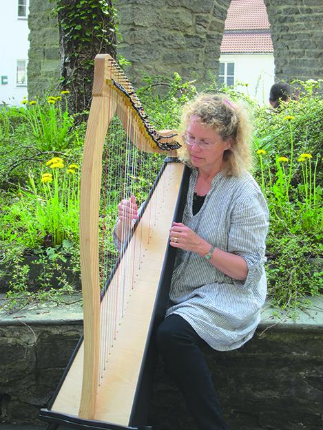 Photo: Jack Kollé Beth tunes her harp at Storetveit Church, Bergen, where the group held a concert.