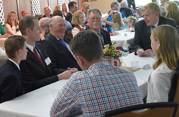 Photos: Sven Gj. Gjeruldsen, The Royal Court of Norway At a reception on his final night in Alaska, His Majesty chats and laughs with young Sons of Norway members at Bernt Balchen Lodge's Viking Hall. Ambassador Aas is at the end of the table, and Bernt Balchen Lodge President is on His Majesty's left.