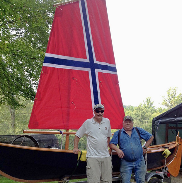 """Photo courtesy of Bernt Balchen Lodge #3-566  Harold Haugaard and John Lunde's fæering once again made a splash at New Jersey's Scandinavian Festival. As Lunde writes, """"We had an enormous turnout for this year's ScanFest. The færing proved to be very popular, with many folks opting for taking a group photo."""" This photo shows the boat's two proud papas at this year's festival. The Norwegian flag sail and rigging were installed just prior to ScanFest."""