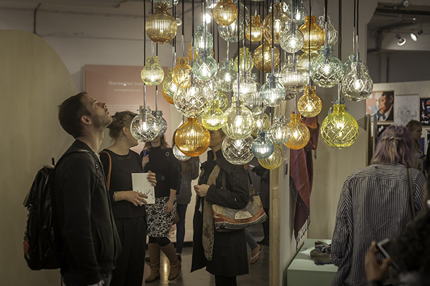 Lit glass pendants hang from the ceiling as part of Hadeland Glassverk's Krystallkule lights, one of the Norwegian designers exhibited in the 100% Norway dent