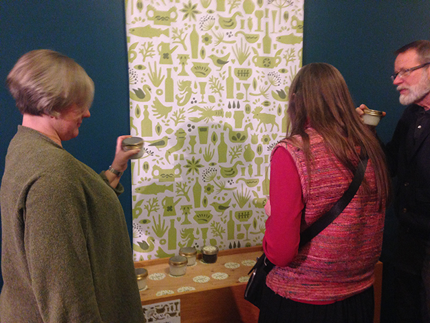 Photo: Gloria Chenoweth / Nordic Heritage Museum Tova Brandt, Skål! exhibit curator, chats with visitors about an interactive activity identifying common aquavit ingredients by their smell.