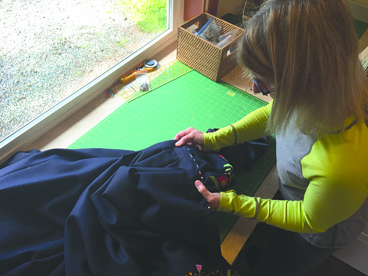 Photo: Linn Chloe Hagstrøm Bunads are made to be refitted throughout a person's life. Here expert Linda Caspersen sews the newly measured vest and skirt back together.