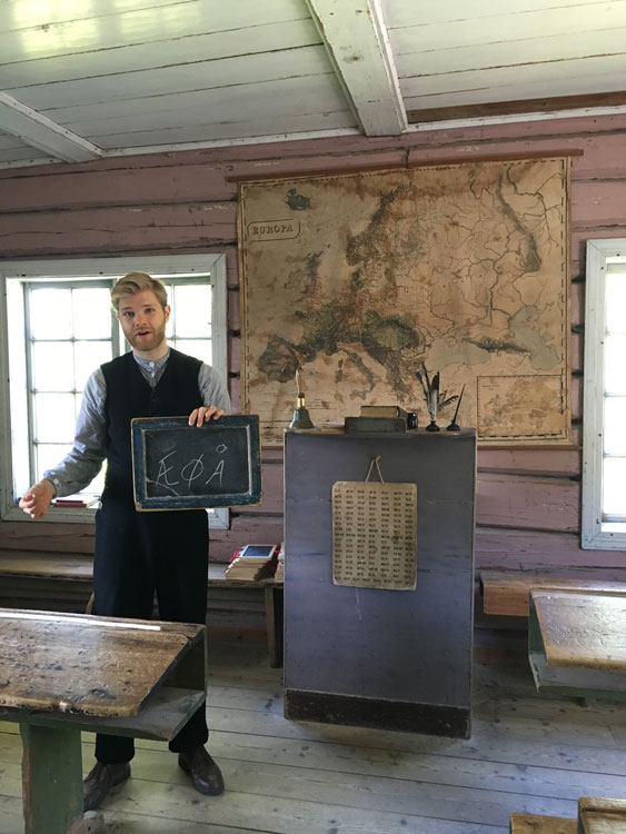 Inside the old schoolhouse at Maihaugen a teacher lectures on the Norwegian vowels—and demonstrates period disciplinary techniques. Photo by Emily C. Skaftun