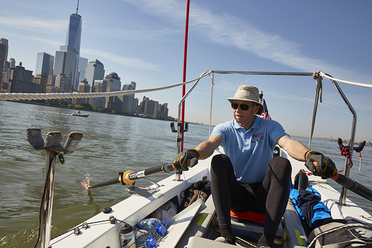 Stein Hoff rowing in a boat with Manhattan in the distance