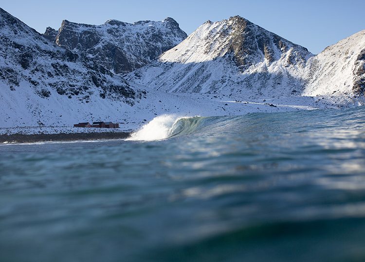 A wave crashes and a snow covered mountain looms in the distance