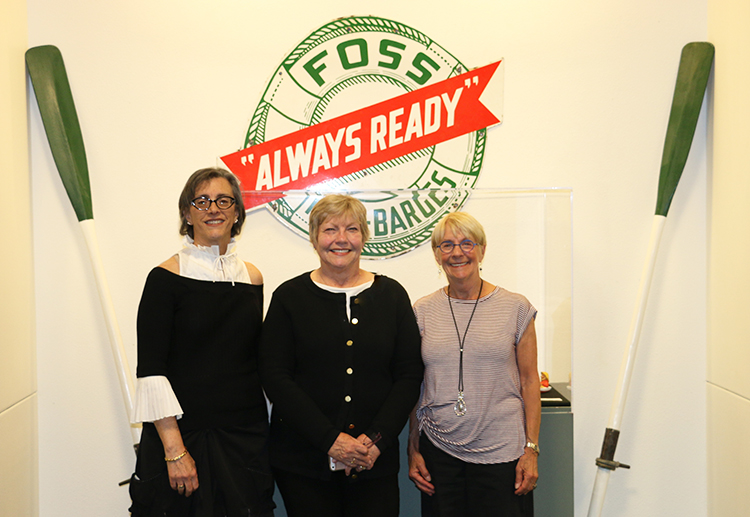 Three women with a connection to Thea Foss stand in front of an exhibit about the Foss barges company.