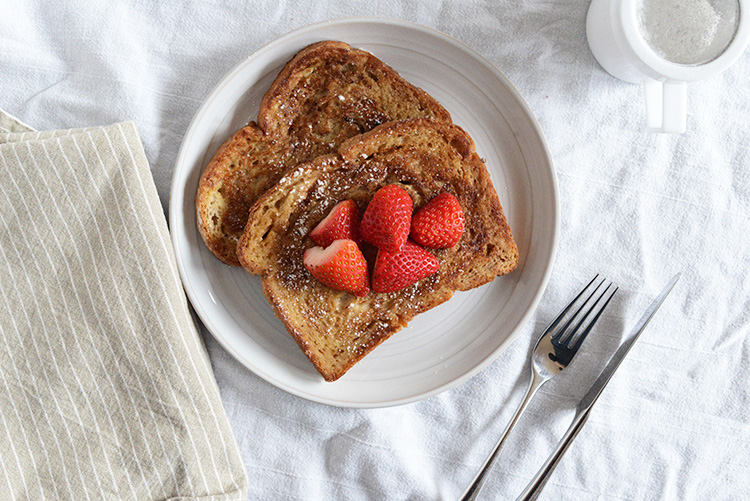 """Arme Riddere, also known as """"Poor Knights"""": two slices of bread topped with powdered sugar and strawberries."""